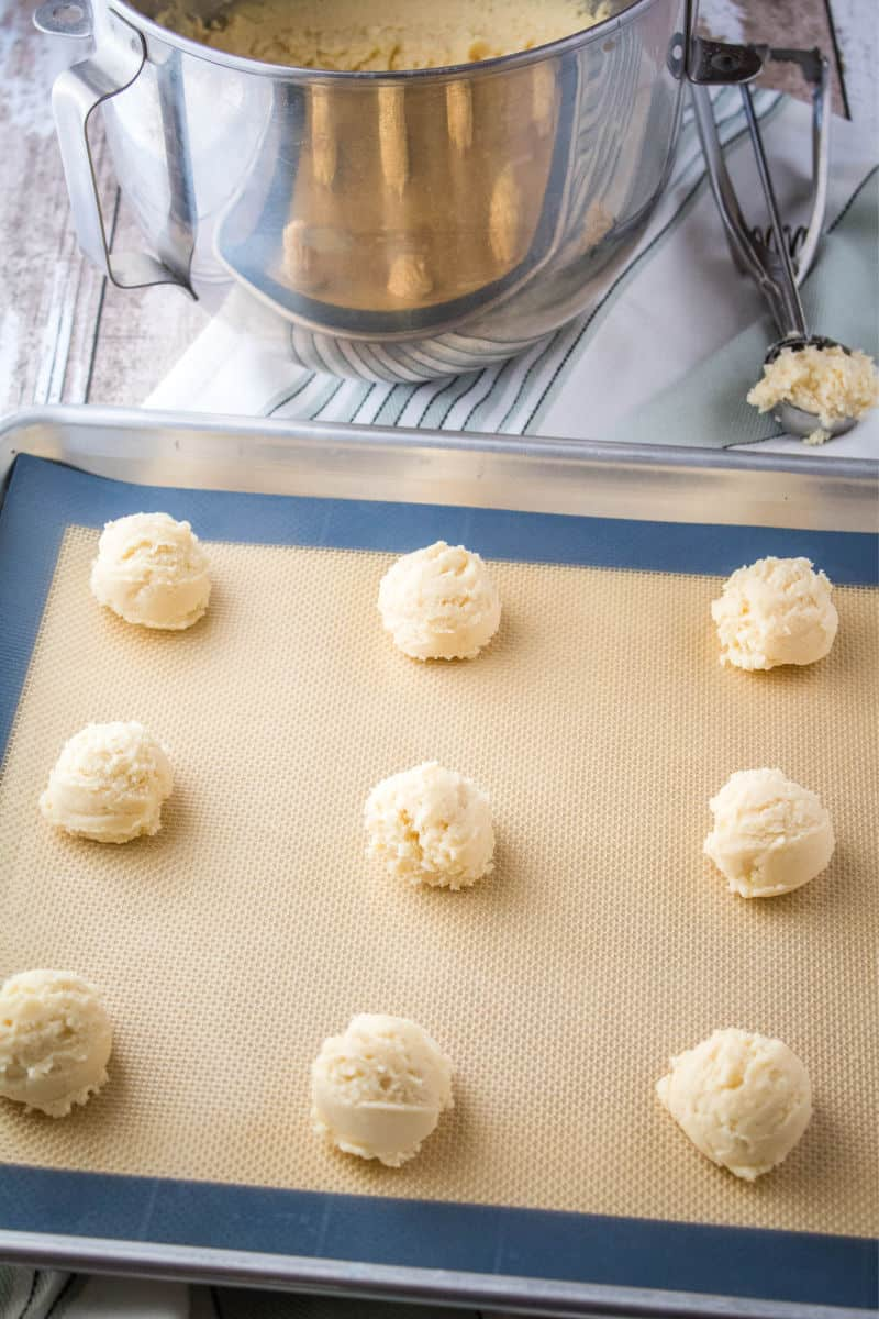cookie dough scooped into balls on a baking sheet