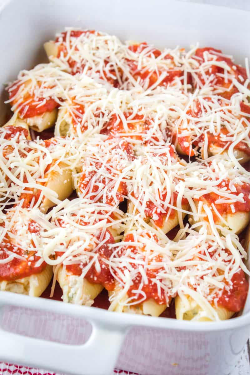mozzarella cheese sprinkled over stuffed pasta shells and sauce