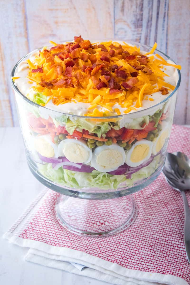 seven layer salad in a trifle bowl with serving spoons