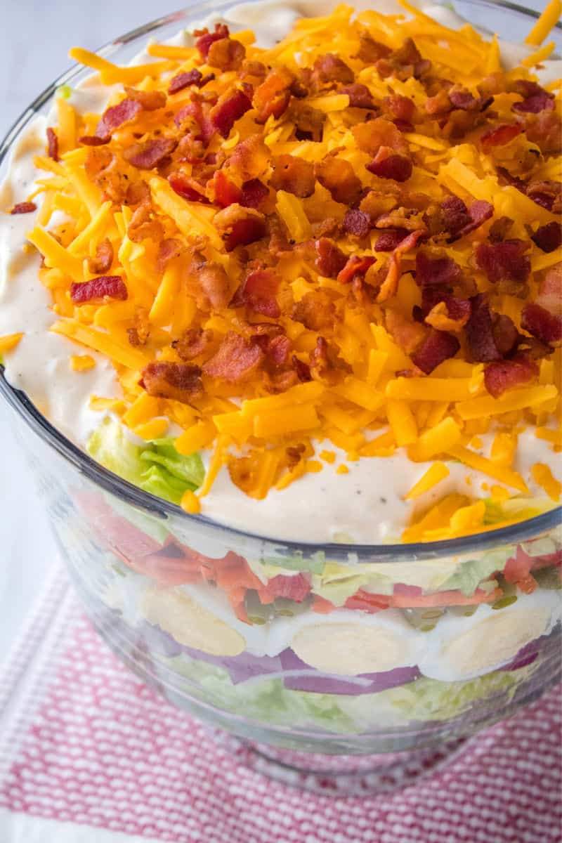 cheese and bacon on top of a layered salad