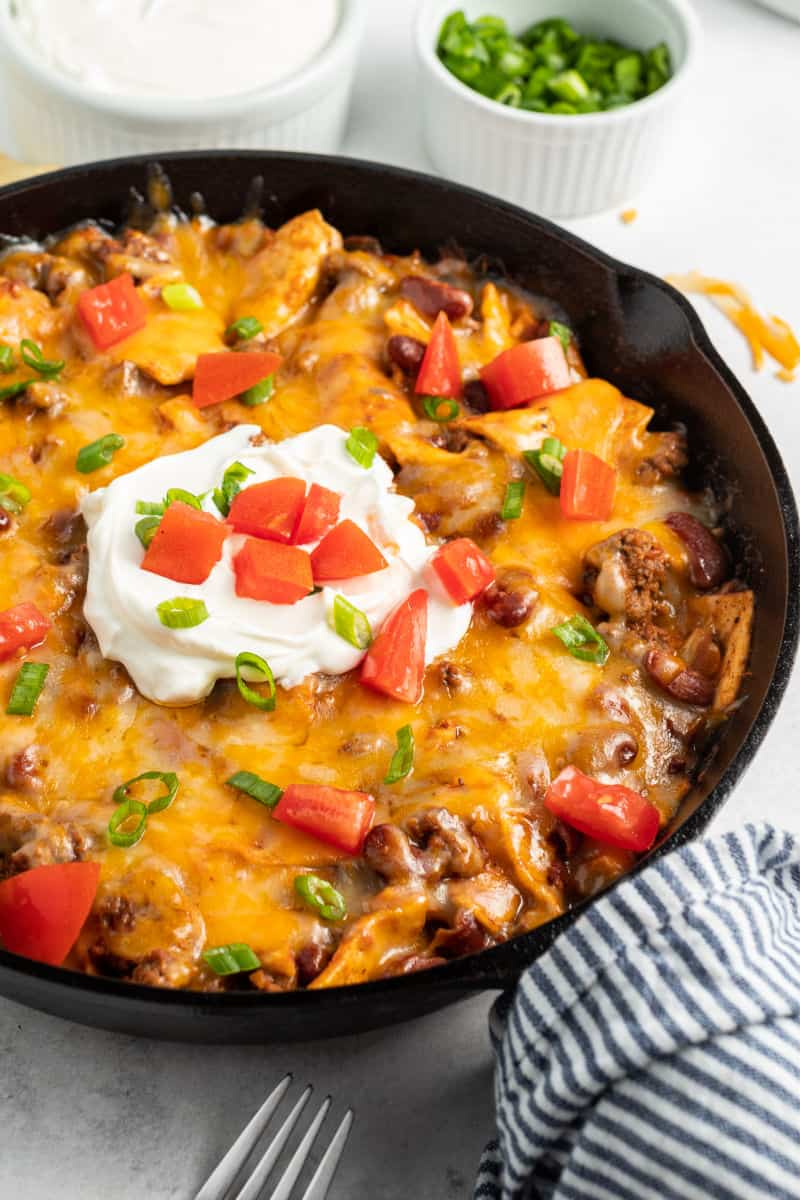 beef burrito skillet topped with sour cream, green onions, and tomato