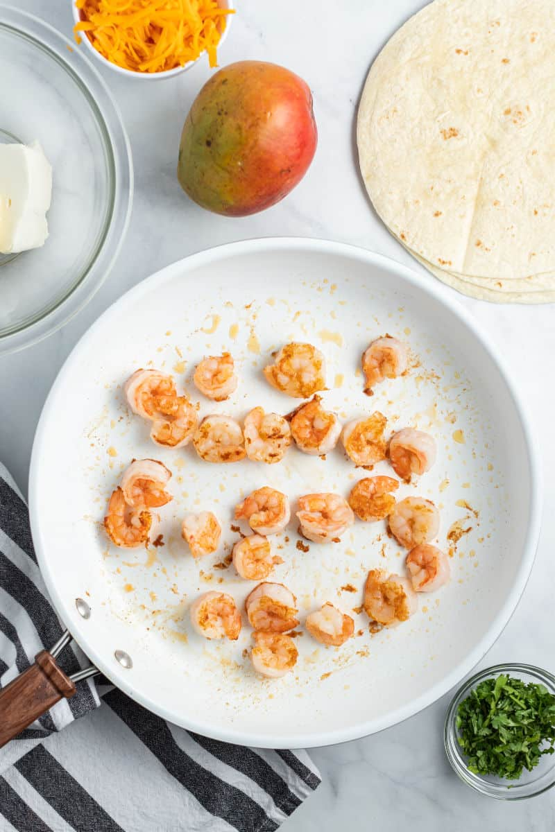 ingreidnets to make mango & shrimp quesadillas with cooked shrimp in a skillet