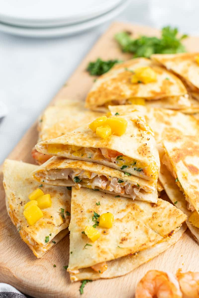 shrimp quesadillas cut into slices and piled up on a cutting board