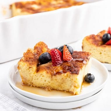square image of a slice of french toast casserole with syrup and berries