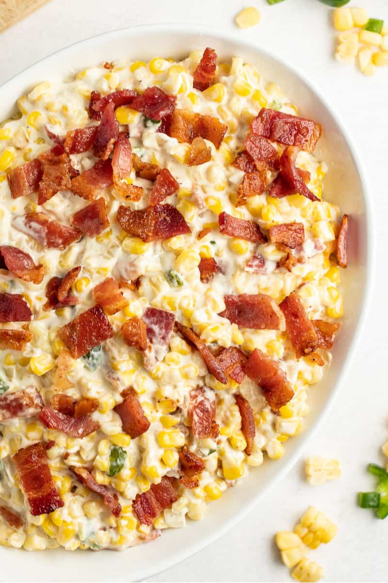 close up of creamed corn in a casserole dish topped with chopped bacon