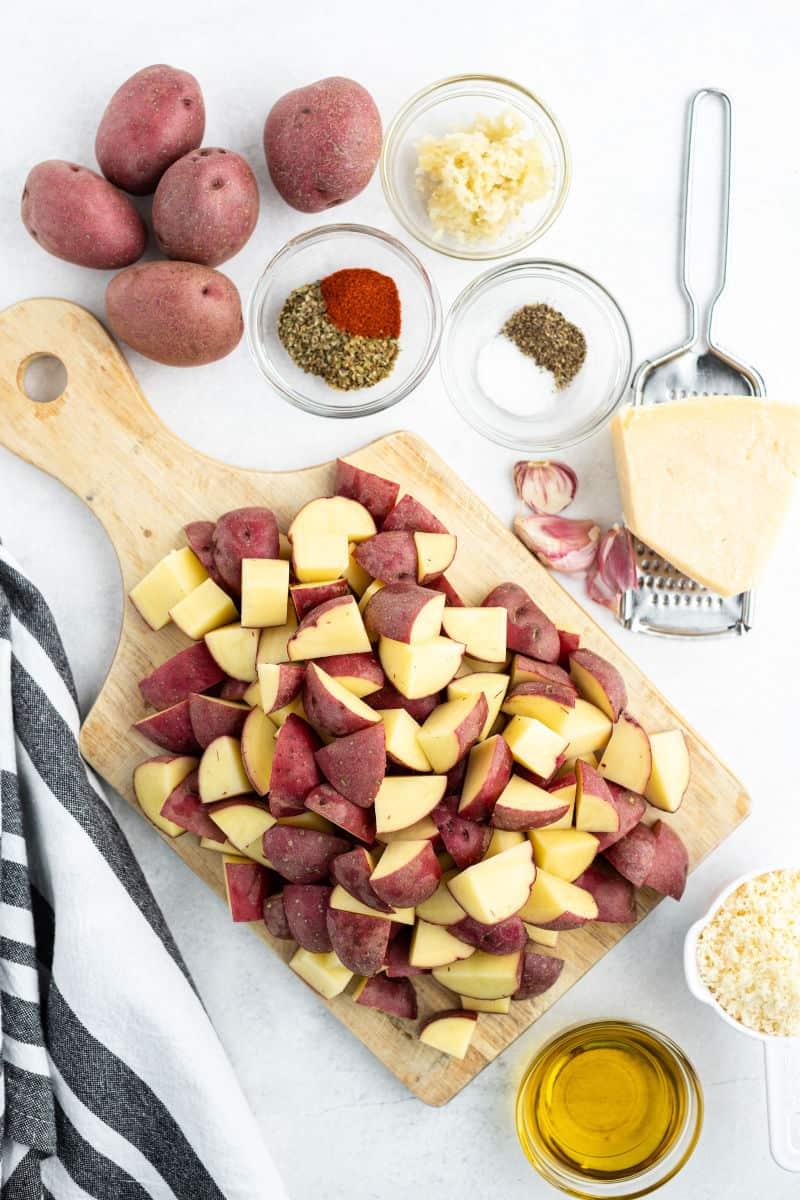 cubed red potatoes on a cutting board with bowls of oil, spices, and Parmesan cheese