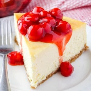 square image of cheesecake with cherries on top and a fork