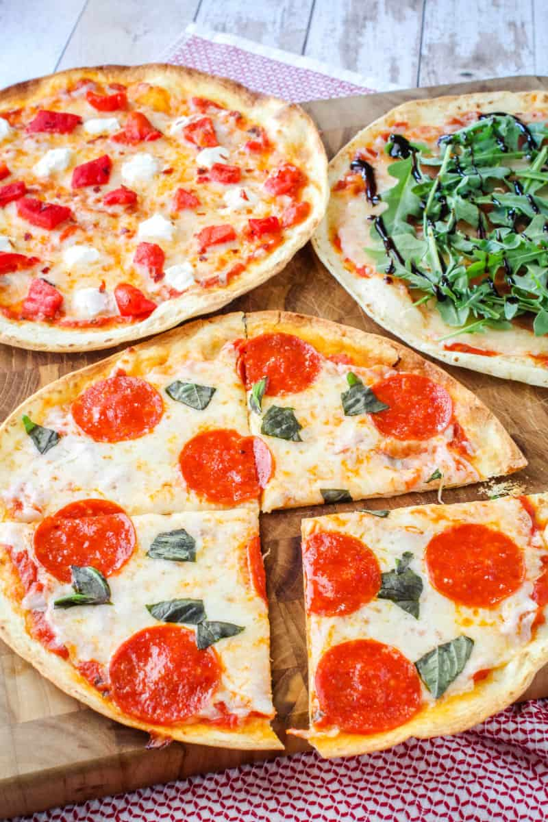 tortilla pizza with pepperoni cut into slices, tortilla pizza with goat cheese & roast red peppers, and tortilla pizza with prosciutto, arugula & balsamic glaze on a cutting board