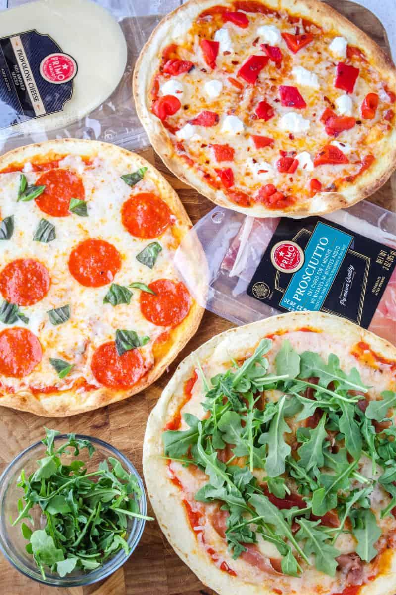 3 types of tortilla pizza - pepperoni, goat cheese & red pepper, and procuitto & arugula on a cutting board with Primo Taglio provolone cheese slices and Primo Taglio prosciutto