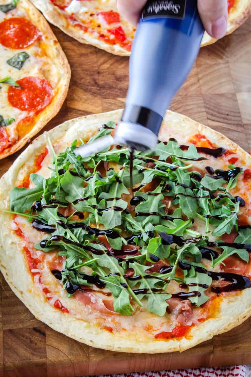 balsamic gaze being drizzled over a tortilla pizza with prosciutto and arugula