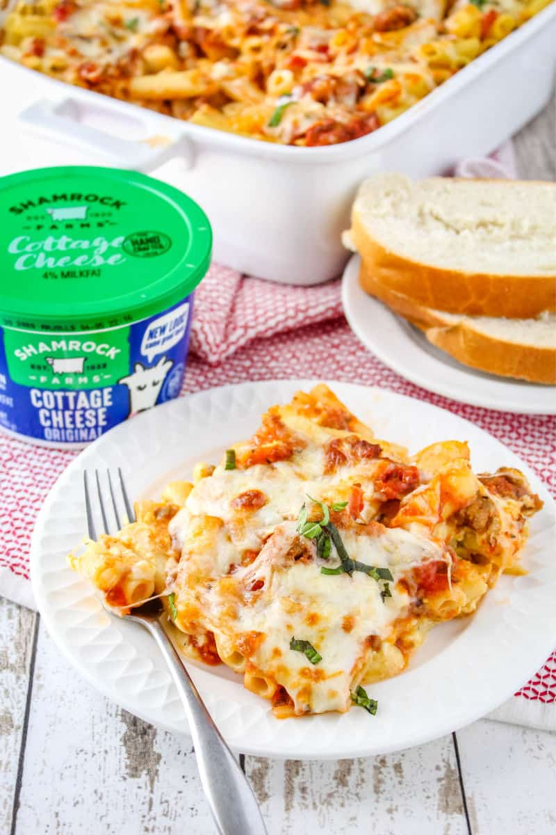 portion of baked ziti on a plate with some sliced bread and a tub of Shamrock Farms cottage cheese