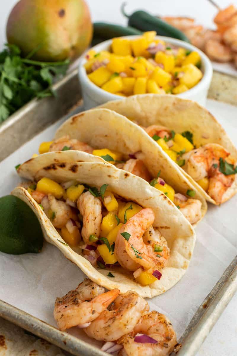 close up of grilled shrimp tacos topped mango salsa