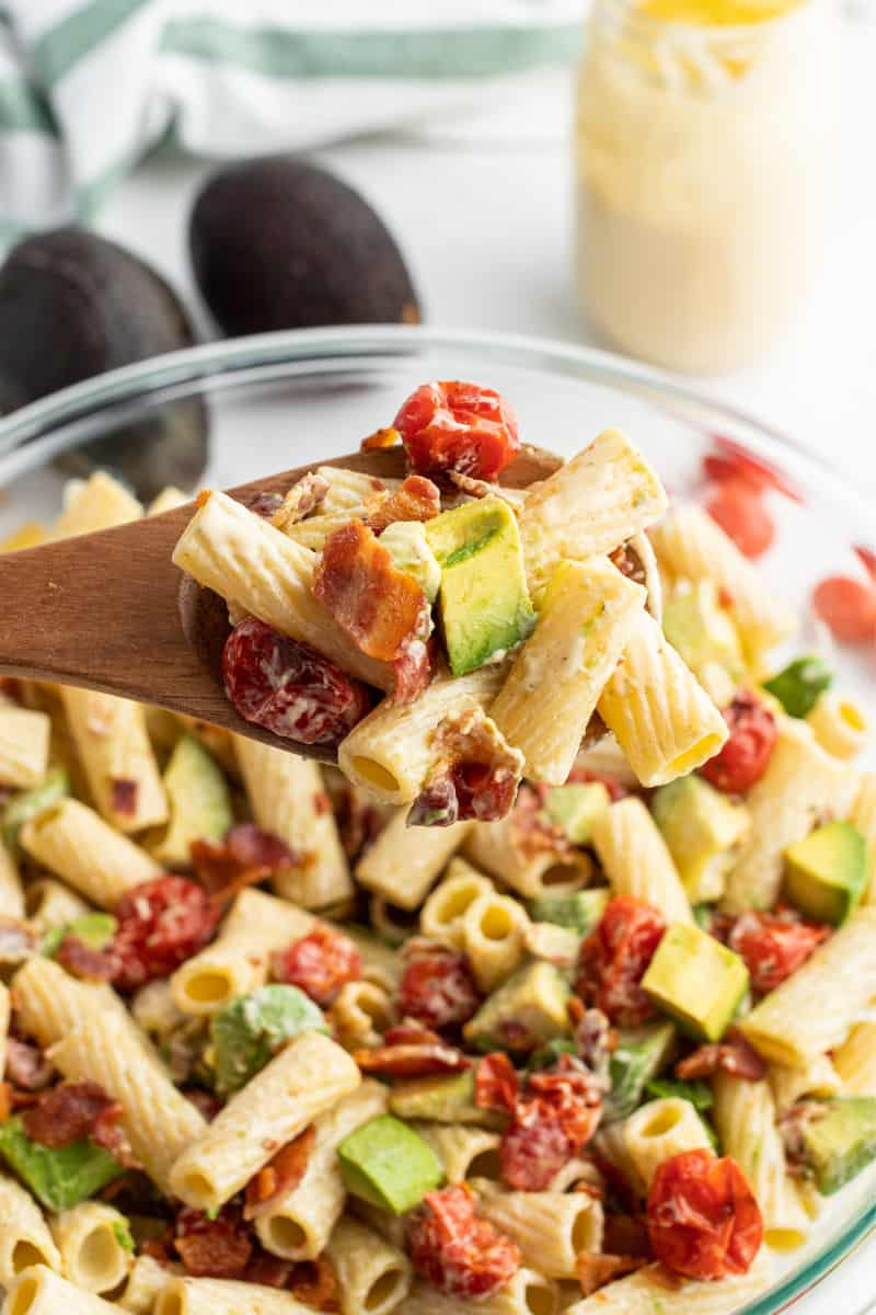 spoonful of avocado pasta salad over the bowl