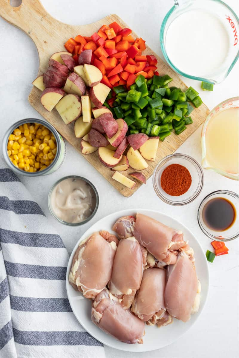 ingredients for crock pot chicken and potatoes - chopped potatoes and bell peppers, canned corn, canned soup, cream, spices, and boneless skinless chicken thighs
