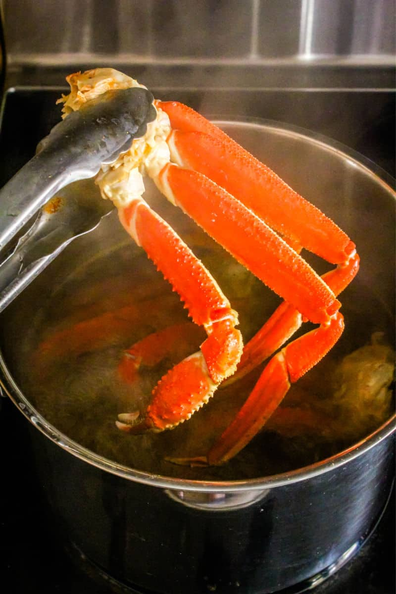 tongs taking crab legs out of a pot of water