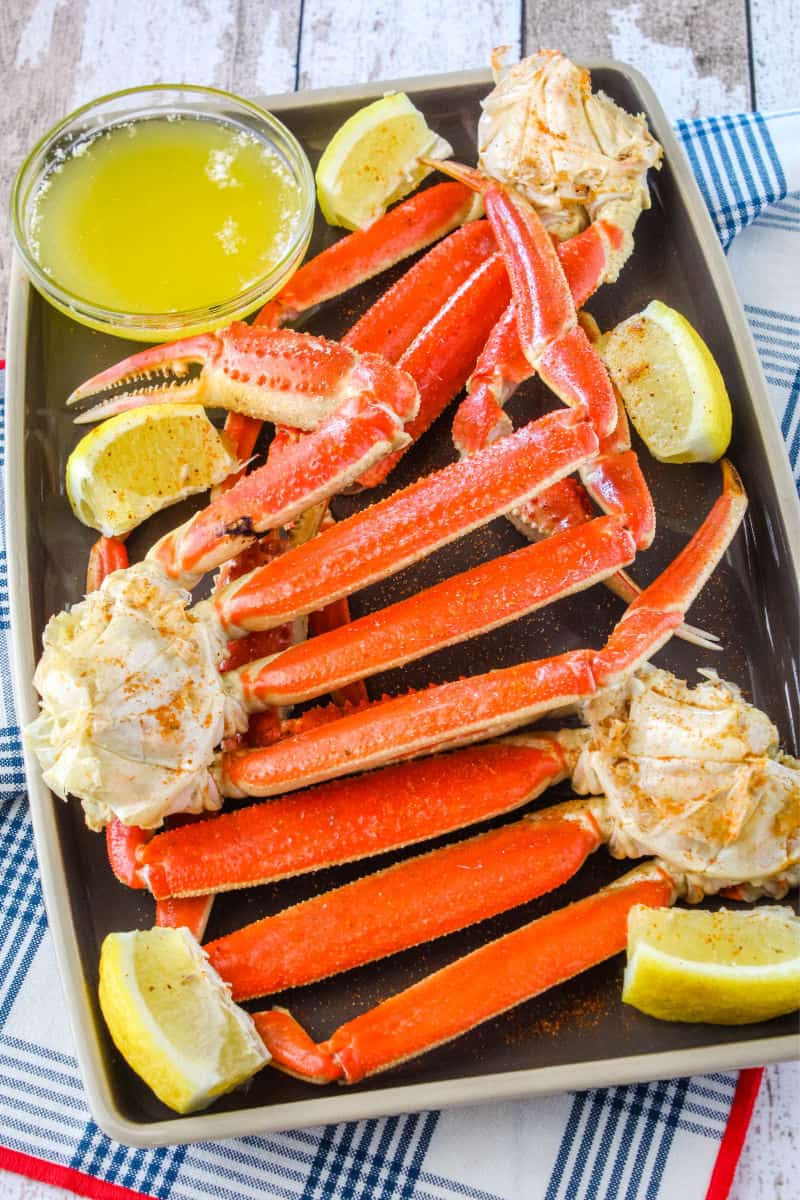 snow crab leg clusters on a plate with clarified butter and lemon wedges