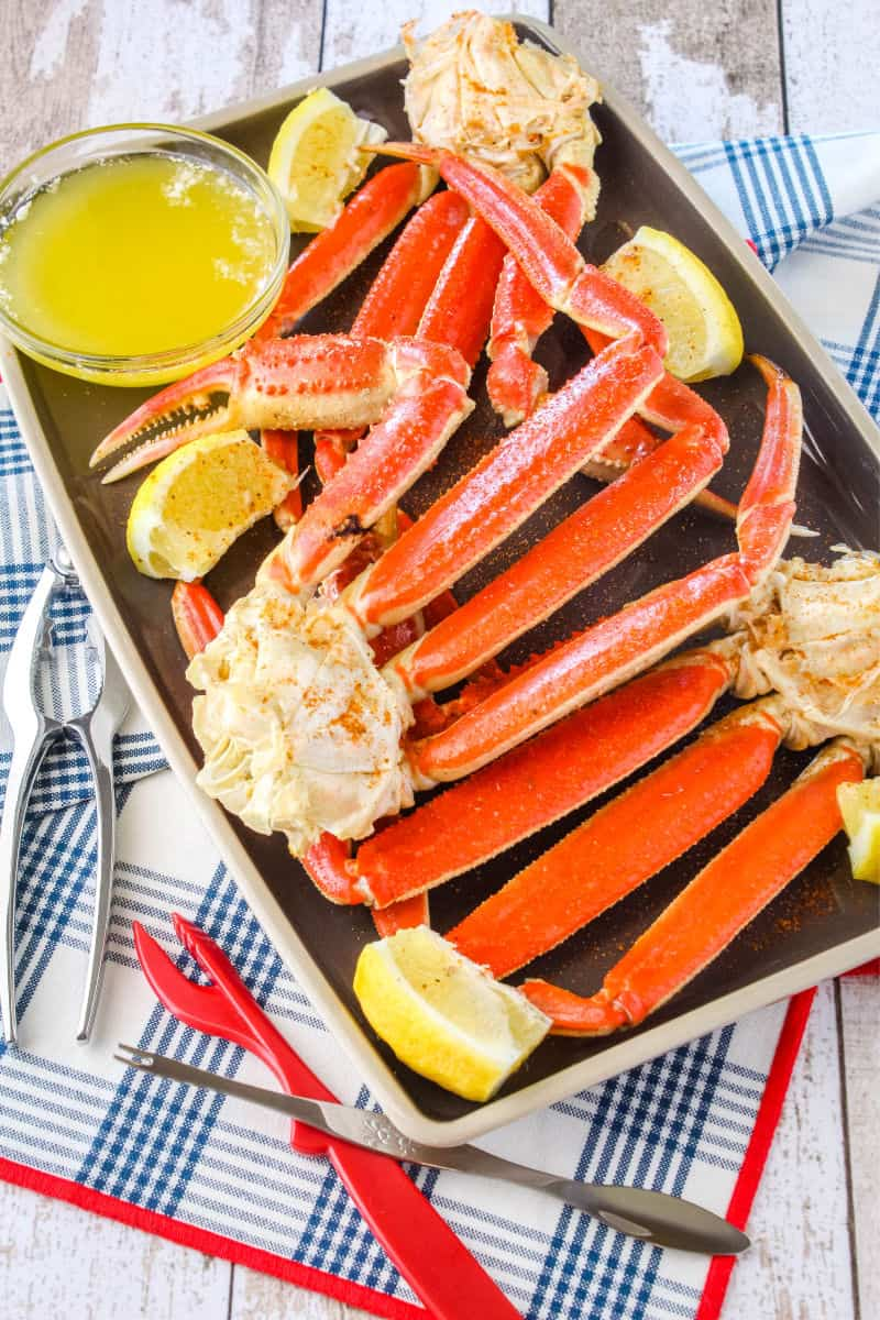 snow crab legs on a plate with butter, lemon wedges, and crab cracking tools
