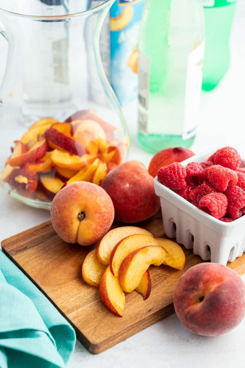 sliced peaches on a cutting board next to whole peaches and a basket of raspberries