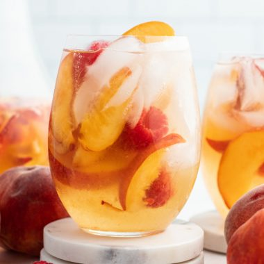 cloe up of a glass of peach moscato punch with raspberries