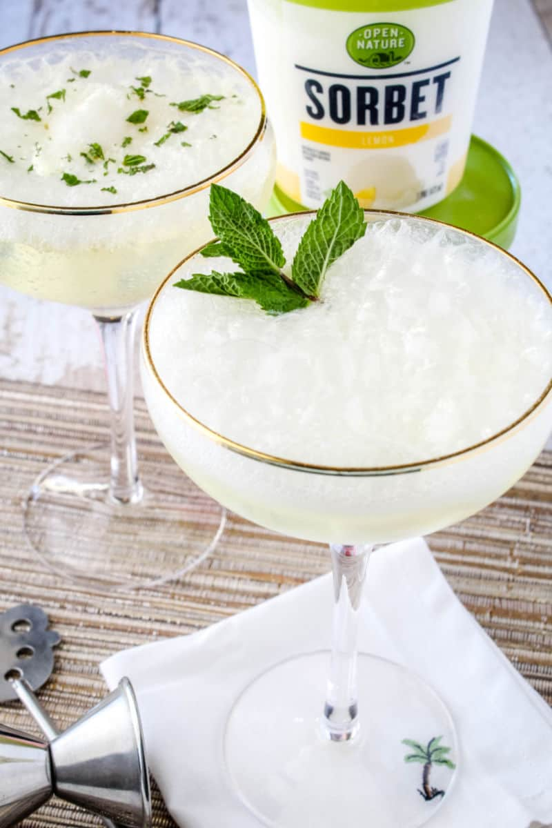 sgroppino cocktail in a coupe glass with a spring of mint, sceond cocktail behind the first with chopped mint sprinkled on top