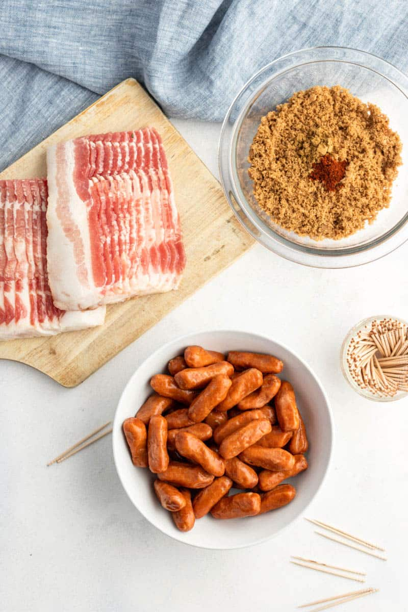 strips of bacon on a cutting board, little smokies sausages in a bowl, and brown sugar with spices in a bowl