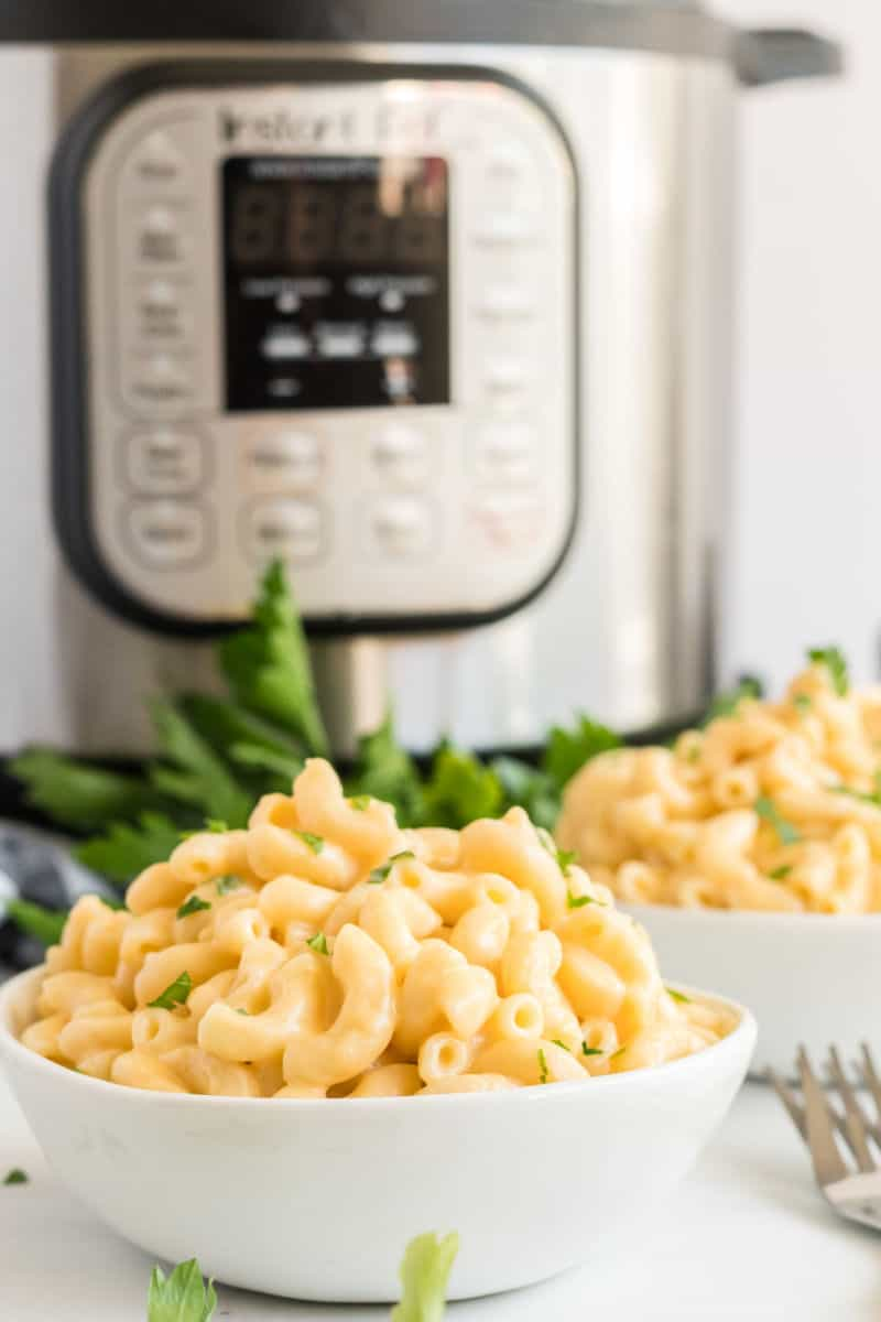 bowls of mac and cheese in front of an instant pot
