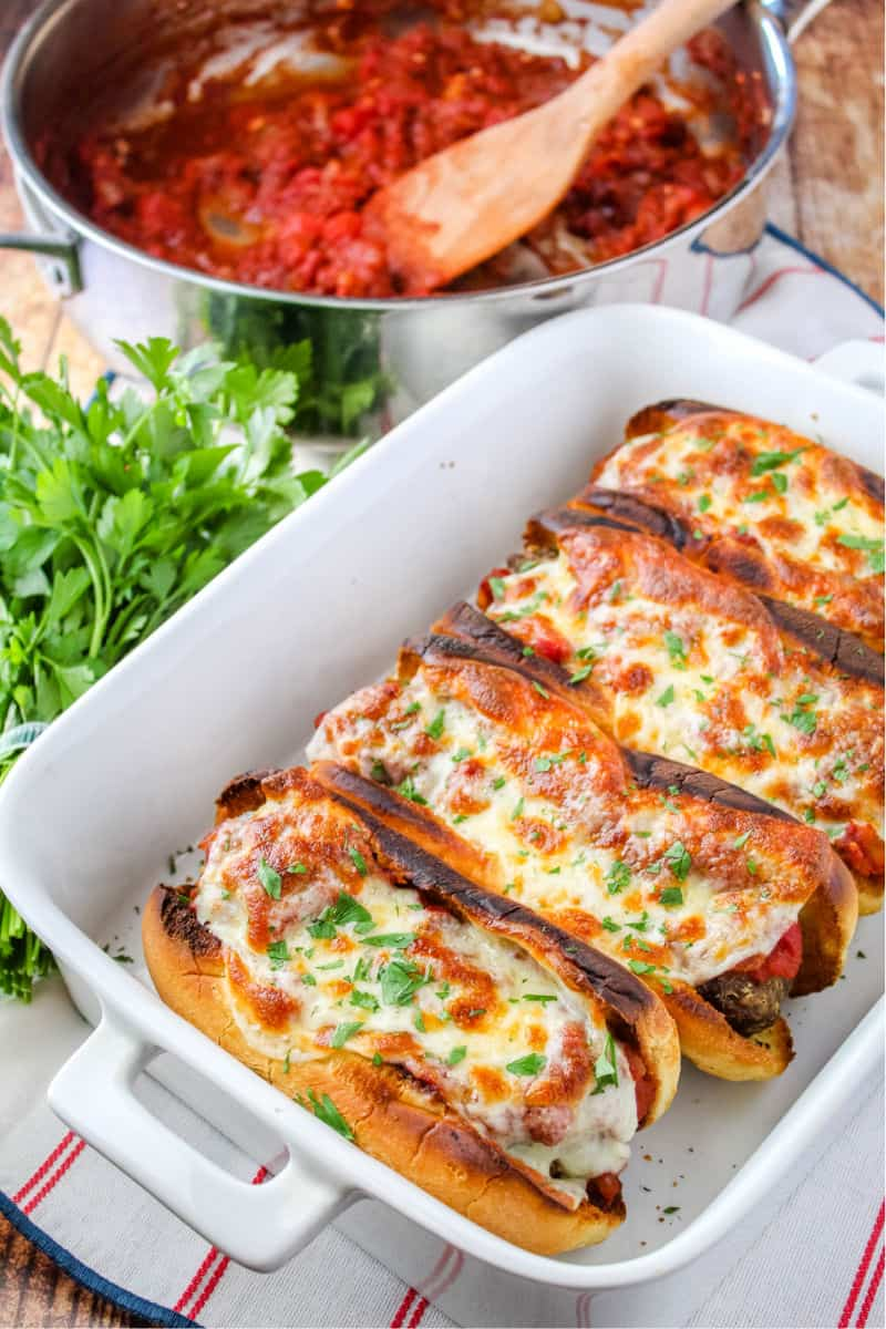 meatballs subs in a baking dish with pan of sauce behind