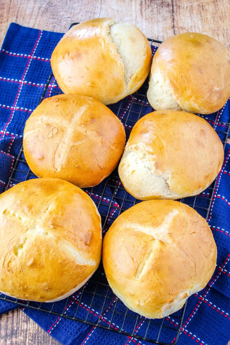 six baked bread rounds on a wire rack