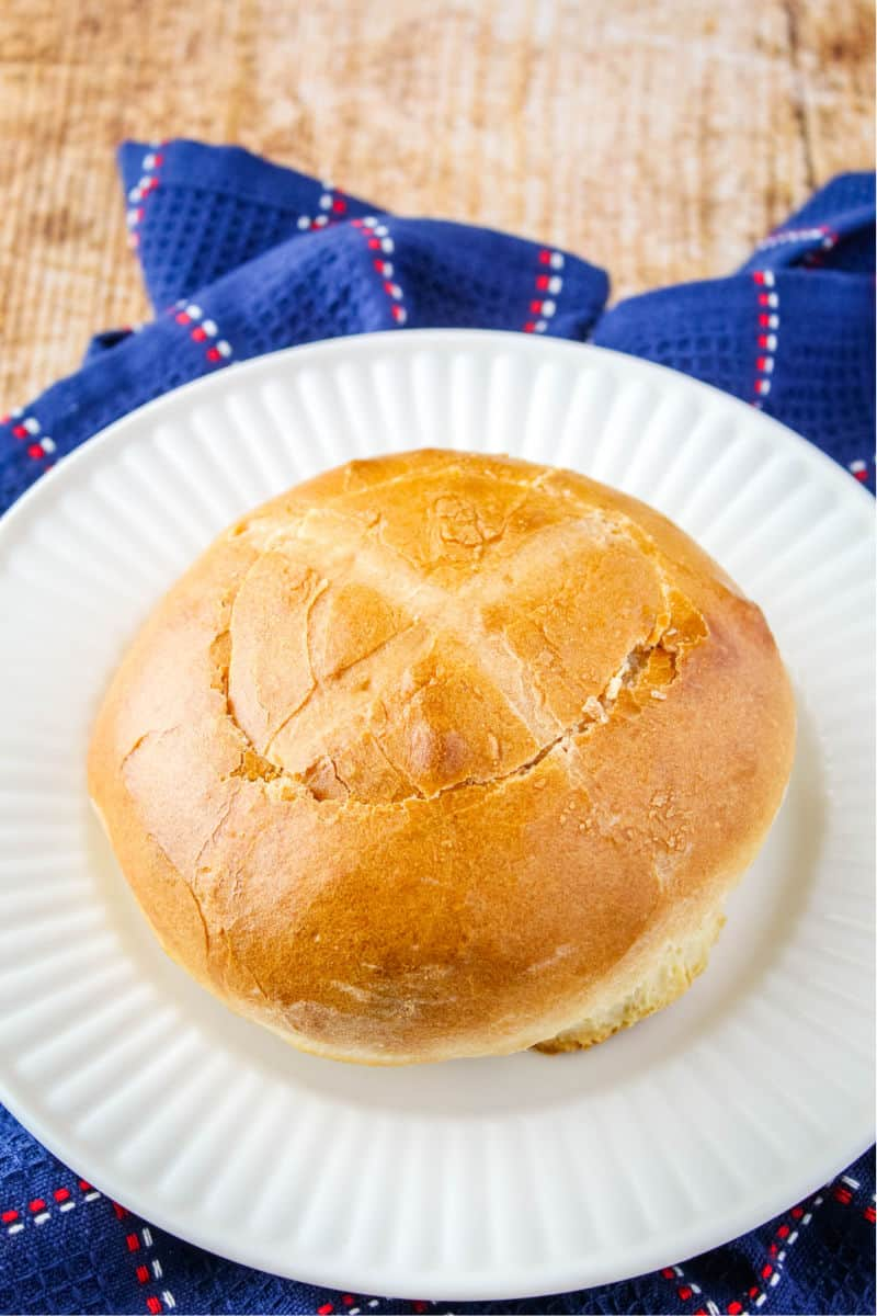 bread round on a plate with a circle cut into the top