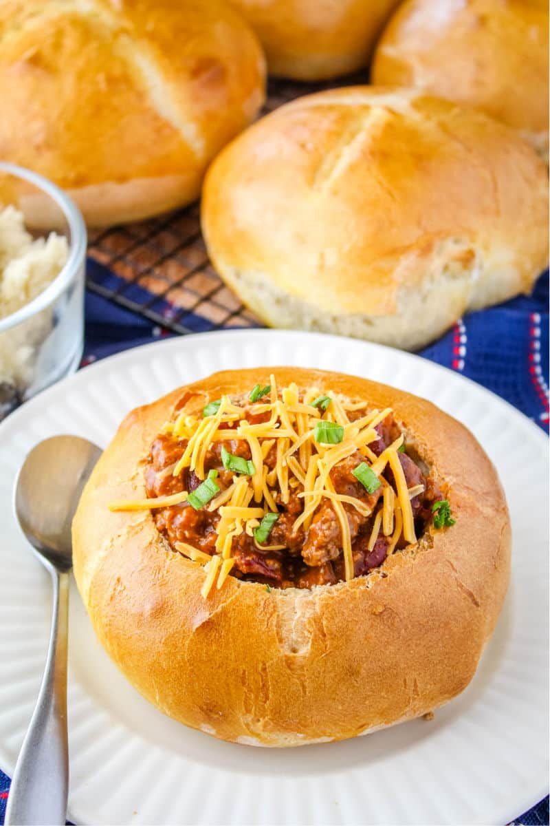 bread bowl on a plate with a spoon and filled with chili topped with cheese and green onions