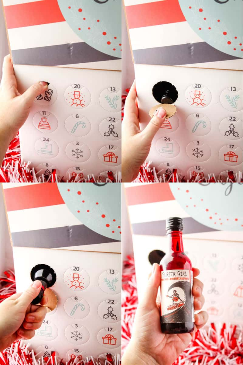 hand opening a wine advent calendar punch out holw and removing wine from the box