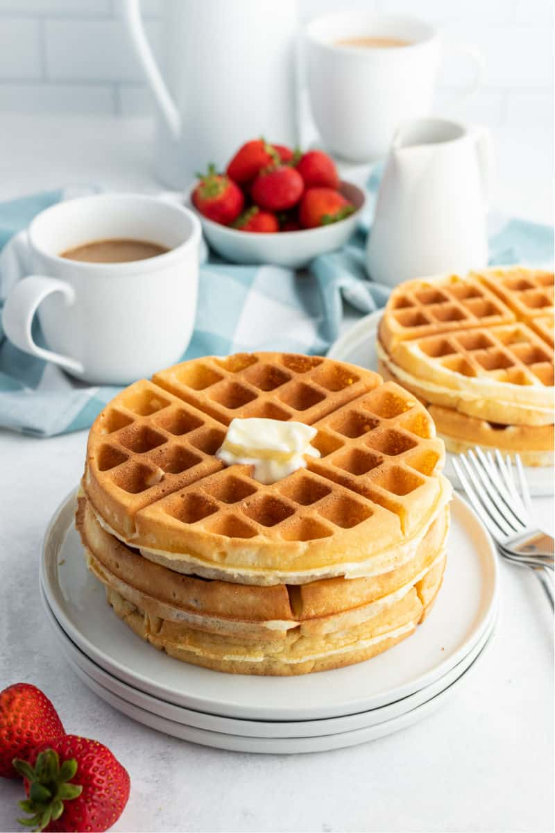 stack of waffles with melting butter on top, cup of coffee and bowl of strawberries in the background