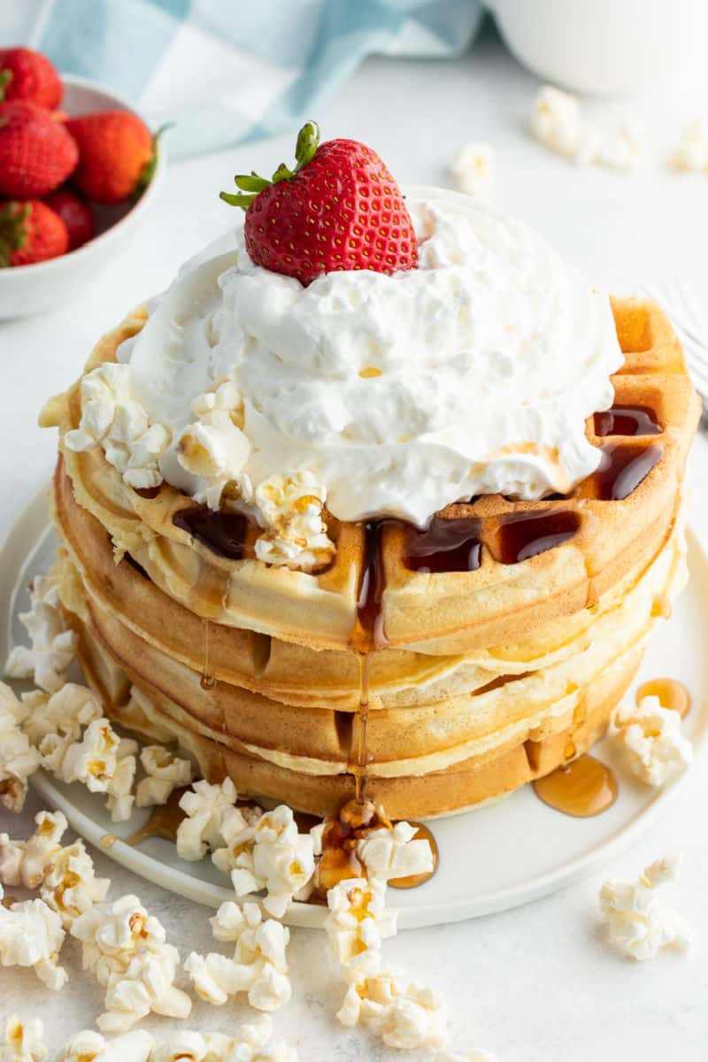 stack of waffles with syrup, popcorn, whipped cream, and a strawberry on top to make together breakfast