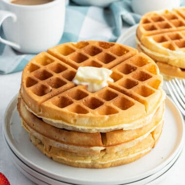 square image of a stack of waffles on a plate with a pat of butter on top
