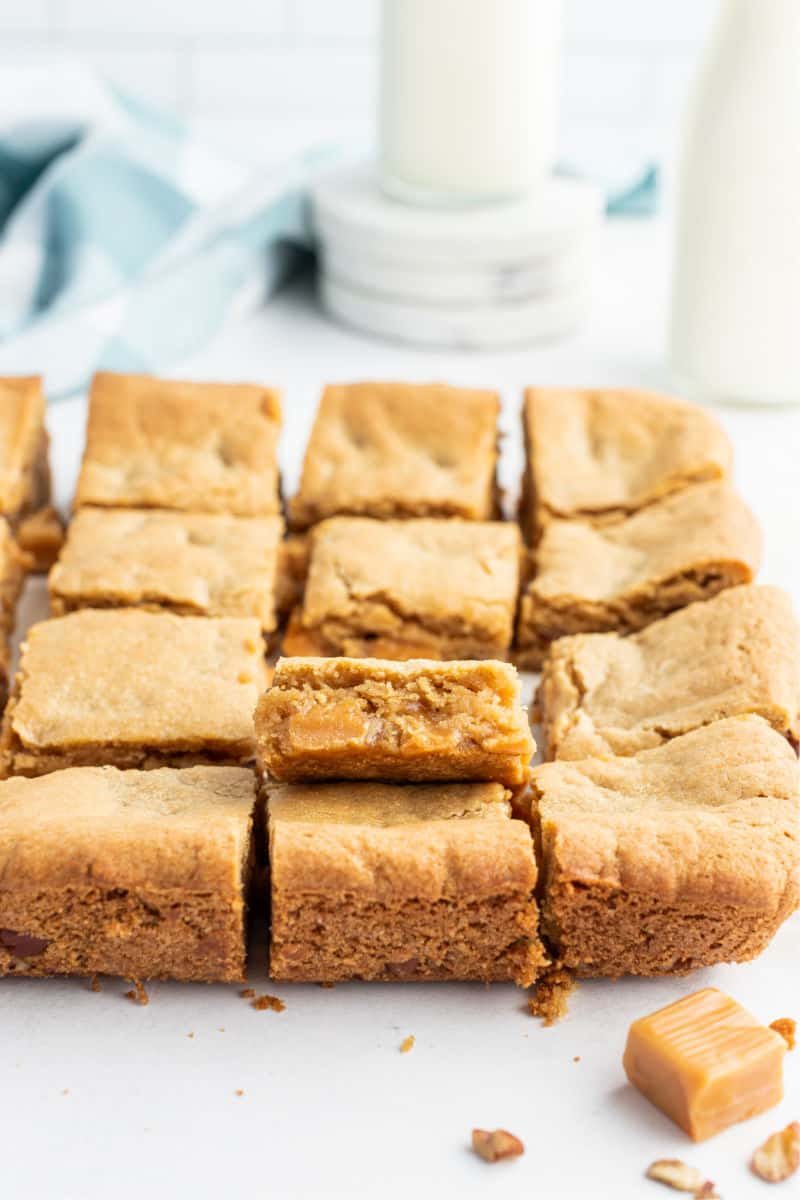 blondies recipe out of pan, cut into bars with one turned up to show caramel and nuts inside