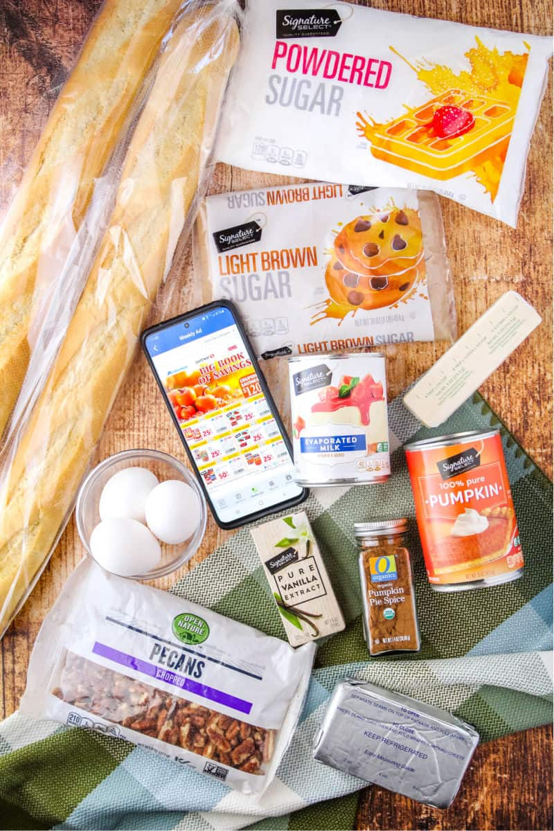 ingreidents to make pumpkin bread pudding laid out with a phone showing Albertsons Fall ads