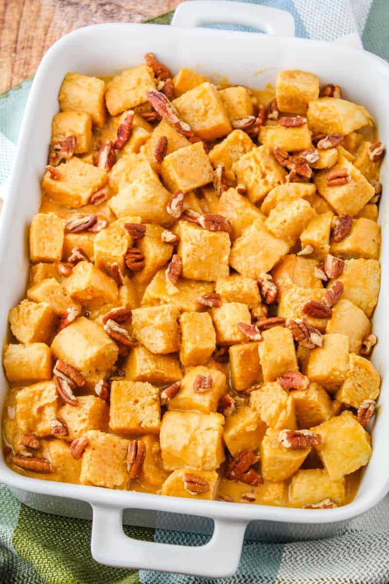 bread cubes in pumpkin crustard with pecans in a baking dish