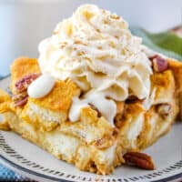 square image of pumpkin bread pudding topped with cream cheese glaze and whipped cream