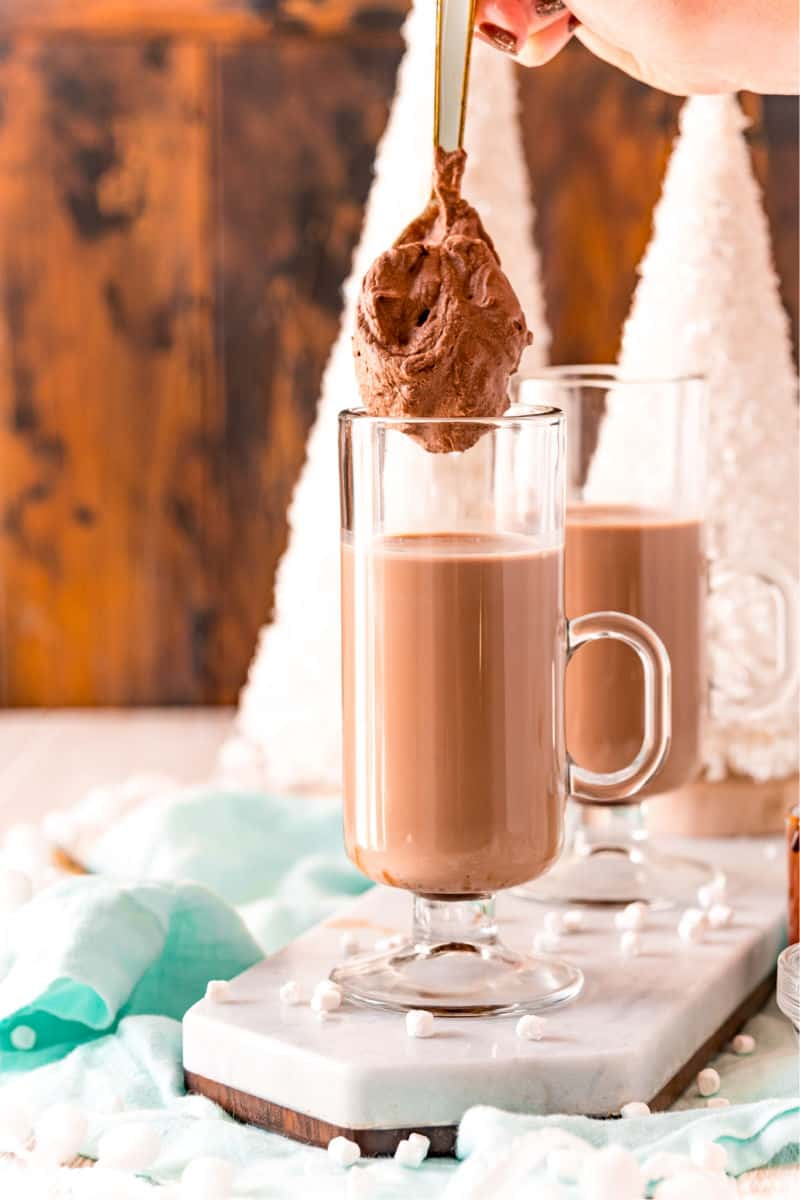 whipped hot chocolate on a spono being added on top of chocolate milk