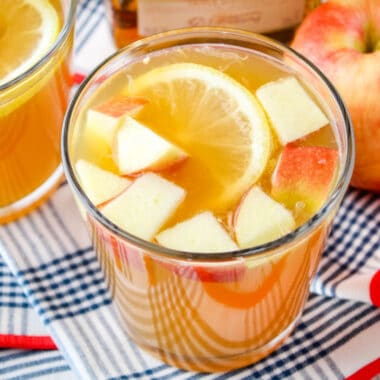 horizontal image of apple cider whiskey punch in a glass next to apples