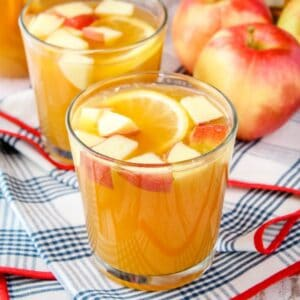 square image of apple cider whiskey punch in a rocks glass with apples and an orange slice