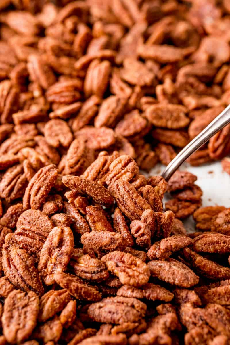 spoon scooping dried candied pecans off a baking sheet