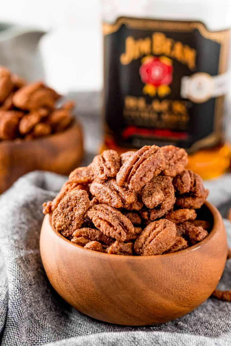 crockpot candied pecans in a wooden bowl in front of a bottle of jim beam black