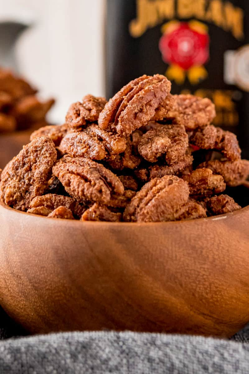 close up of candied pecans in a wooden bowl