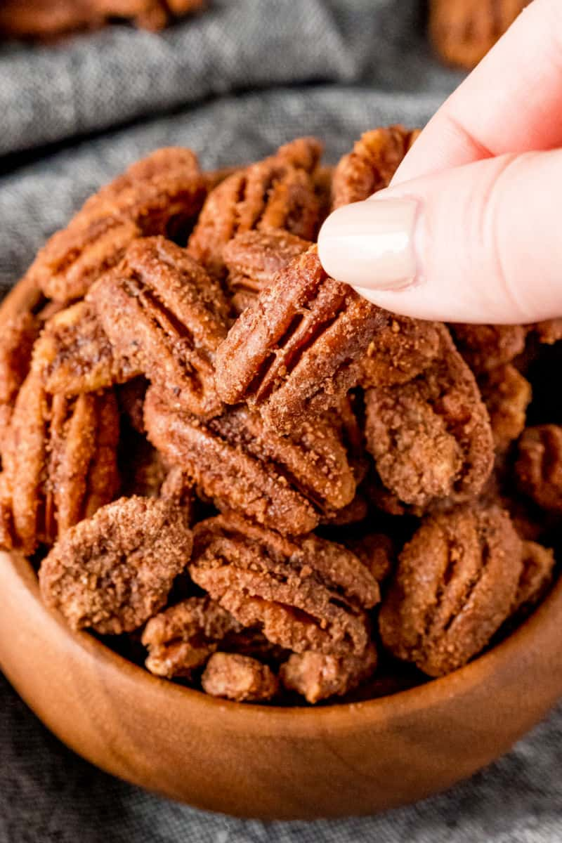 fingers taking candied pecan from a bwol