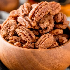 square image of candied pecans in a wooden bowl