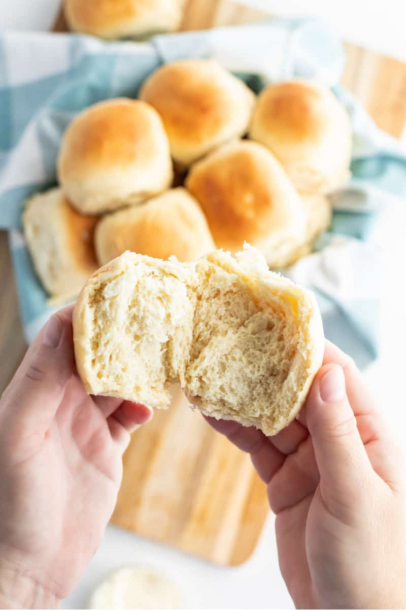 hands pulling open a dinner roll to show texture inside