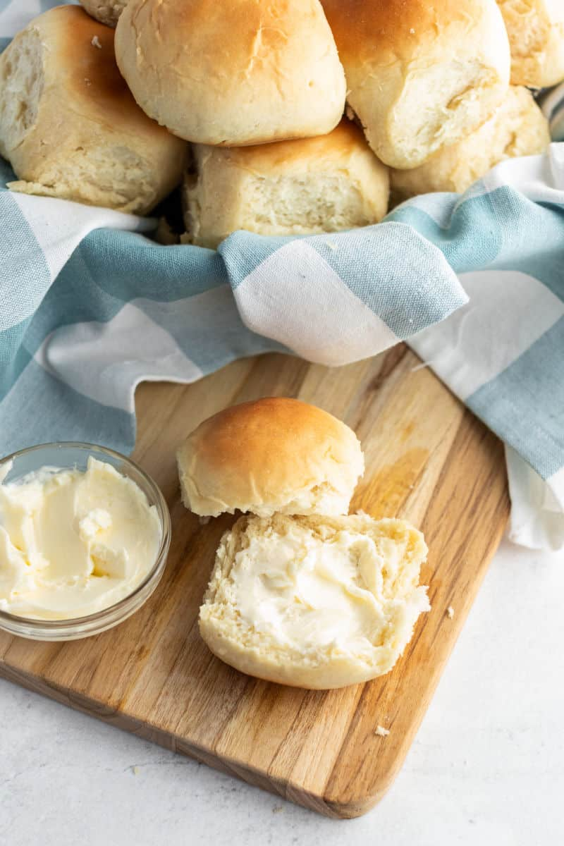dinner roll broken in half and spread with butter, top hafl overlaying bottom half with butter, basket of roll in the background