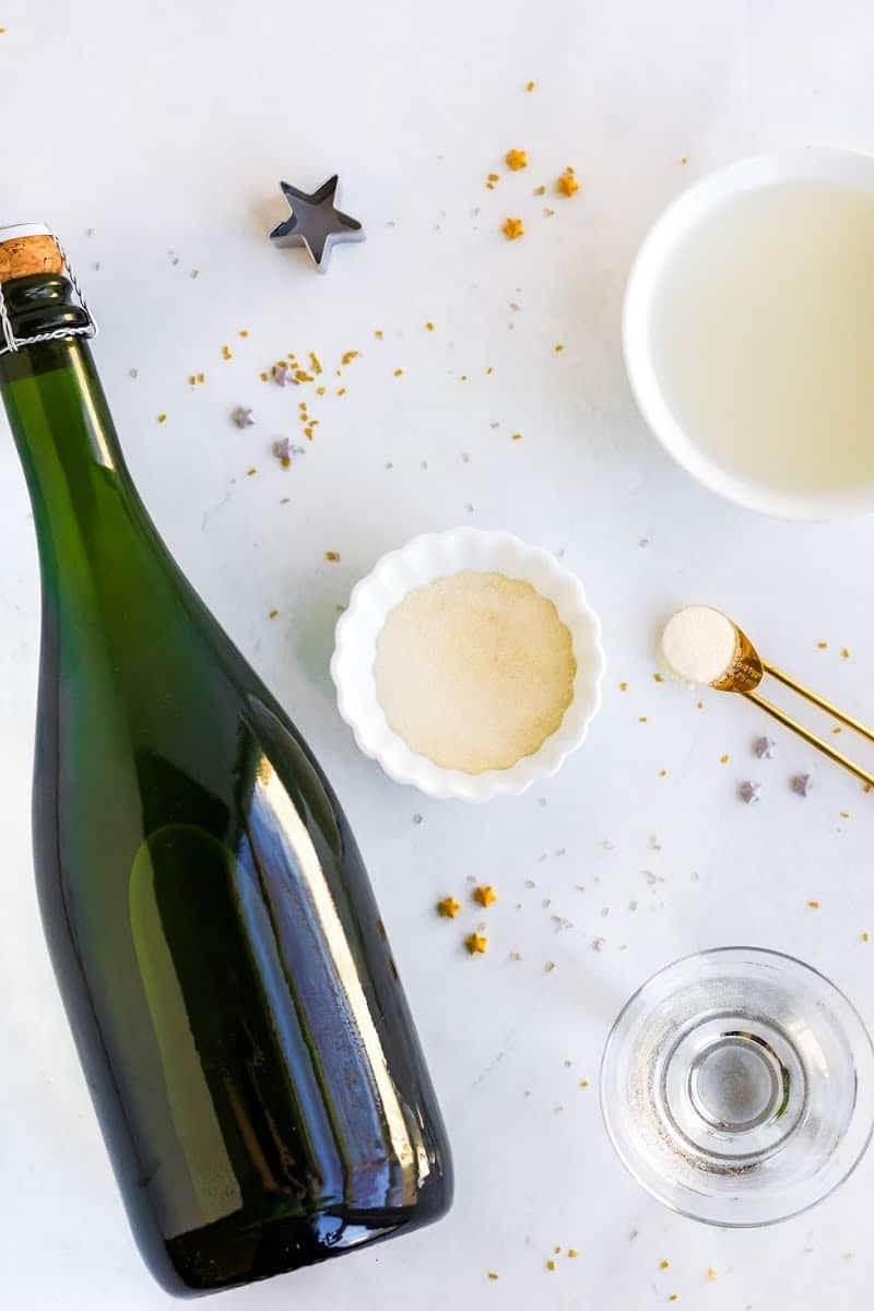 ingredients to make champagne jello shots laid out on a countertop with star sprinkles