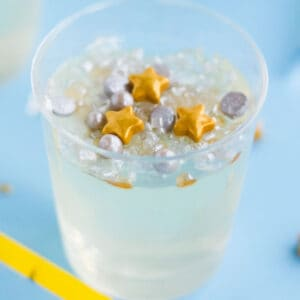 square image of champagne jello shots in a clear platsic cup with gold and silver sprinkles on top